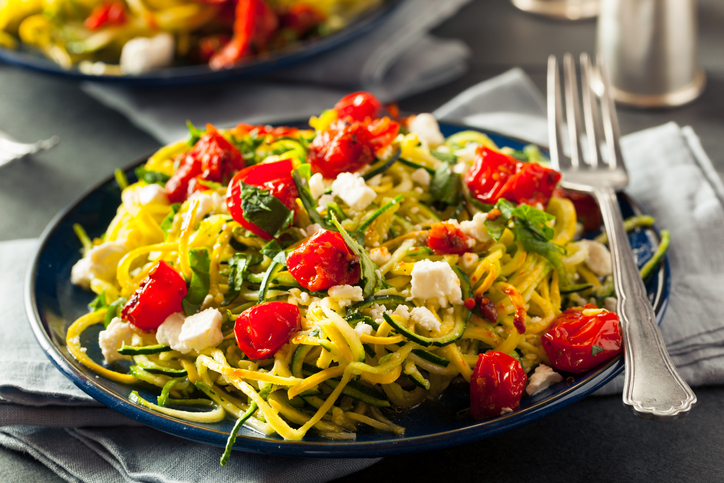 plate of zucchini noodles with feta cheese and tomatoes