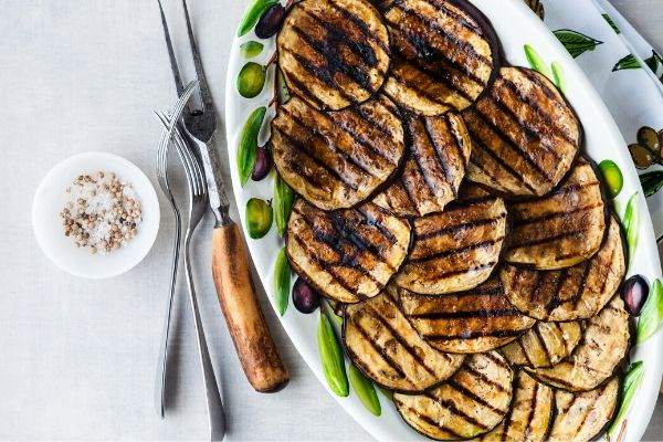Plate of Weight Watchers Spicy Grilled Eggplant on plate with grilling utensils on the side