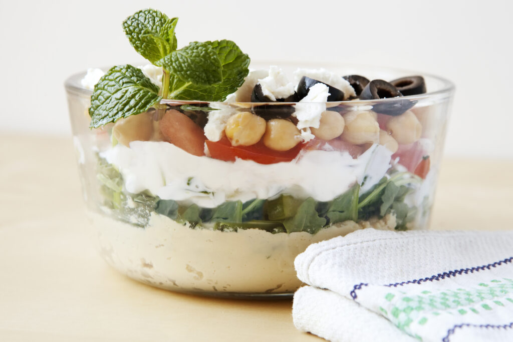 Easy From Scratch Layered Hummus Dip in a clear glass bowl topped with fresh herbs