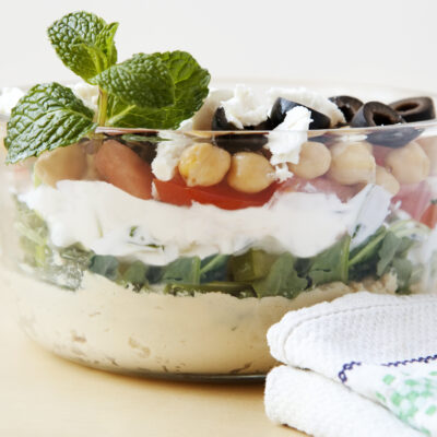 Easy From Scratch Recipe for Layered Hummus Dip + Weight Watchers Recipe shown layered in a glass bowl