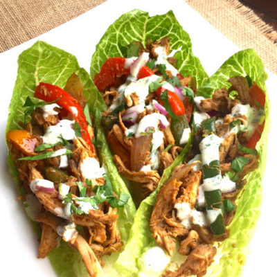3 Skinny Chicken Fajita Romaine Wraps with Creamy Cilantro Lime Sauce on white plate