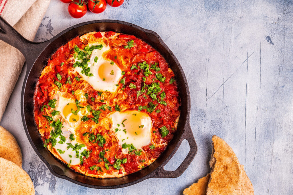 Weight Watchers Egg Shakshuka in a Frying Pan. Eggs Poached in Spicy Tomato Pepper Sauce.