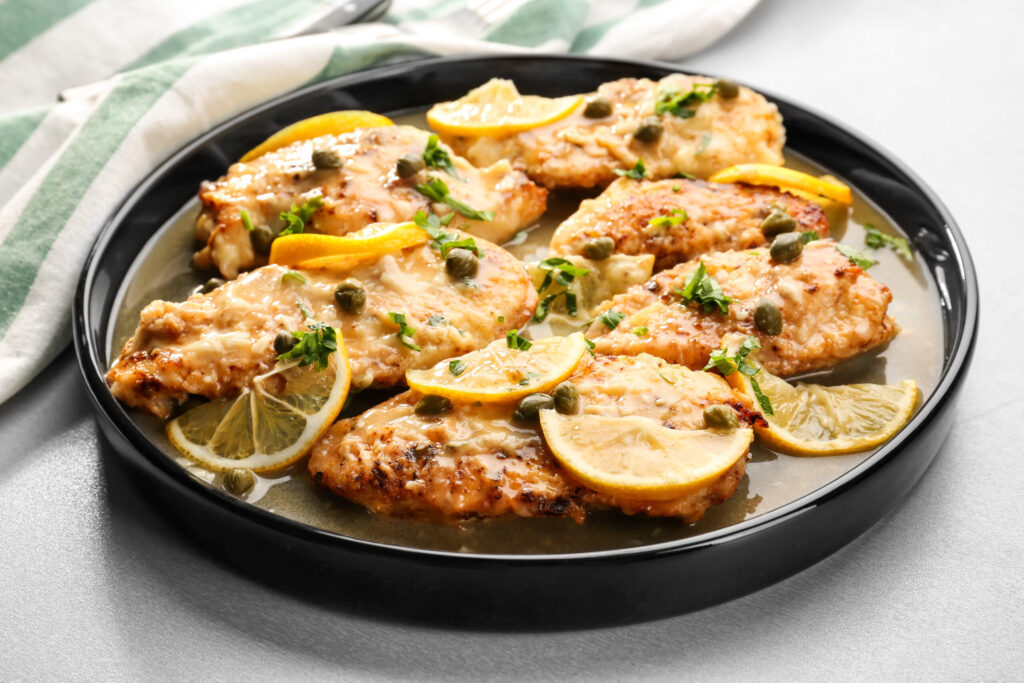 Slow Cooker Chicken Piccata on Black Plate using Healthy Chicken Breast