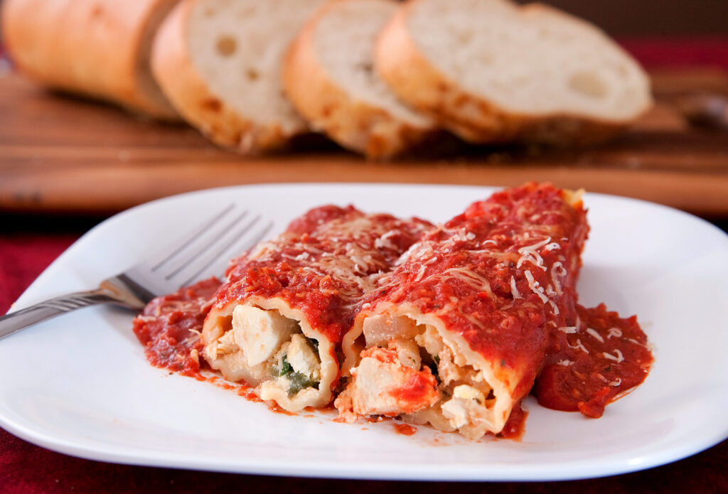 Healthy Cheesy Chicken Manicotti on white dinner plate made with boneless chicken breasts
